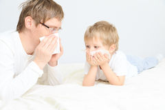 Father and son wiping nose Stock Images