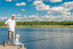 father and son on a wooden pier on a sunny day Stock Photo