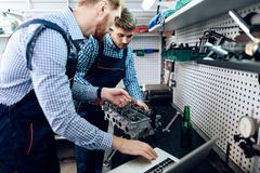 Father and son work at the auto service. Two mechanics work with the details of the car. Stock Image