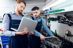 Father and son work at the auto service. Two mechanics work with the details of the car. Royalty Free Stock Photography