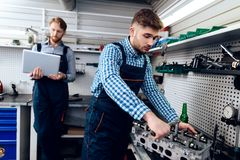 Father and son work at the auto service. Two mechanics work with the details of the car. Royalty Free Stock Photos