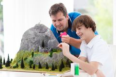 Father and son work on model building project. Father and son work on model building school project. Kids and parent build miniature scale model mountain for Stock Photo