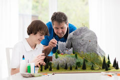 Father and son work on model building project. Father and son work on model building school project. Kids and parent build miniature scale model mountain for Stock Photos
