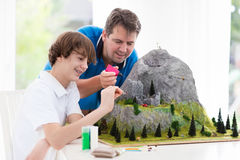Father and son work on model building project. Father and son work on model building school project. Kids and parent build miniature scale model mountain for Stock Image