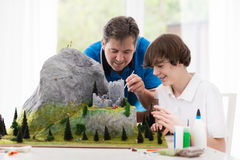 Father and son work on model building project Stock Photography