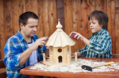 Father and son working on bird house together. Polishing it with sand paper royalty free stock photos