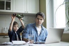 Little son disturbing working freelancer father. Father and son working on laptop. businessman working from home and watching child. spending time with kid stock images
