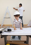 Father and son working with plans at home Stock Image