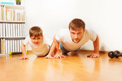 Father and son working up, doing pushups at home Royalty Free Stock Image