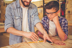 Father and son working with wood stock photography