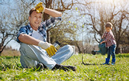 Father and son working in yard together. What a busy day. Shot of a mature men holding a thermos mug, sitting on the grass and having a rest while his son Royalty Free Stock Photography