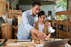 Father and son in workshop. Carpenter showing video on laptop to his son before working with wood stock photo