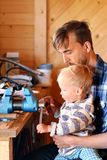Father and son in workshop. Dad teaches his child to use tools. Fatherhood and transfer of experience concept.  royalty free stock images