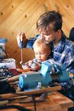 Father and son in workshop repairing some stuff. Cute boy explor. Ing tools. Fatherhood concept stock image