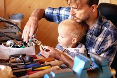 Father and son in workshop repairing some stuff. Cute boy explor. Ing tools. Fatherhood and transfer of experience concept royalty free stock images