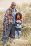 Father And Son Wrapped In Blanket Amongst Dunes On Stock Photo