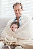 Father and son wrapped in a blanket on the couch Royalty Free Stock Photo