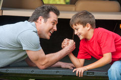 Father and son is wrestling at the pened car boot. Royalty Free Stock Photography