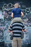 Father and son writing on big blackboard Royalty Free Stock Images