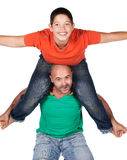 Father and son. Young caucasian boy wearing an orange t-shirt and blue jeans is playing with his father. The dad is wearing a green shirt. The boy is on the Stock Image