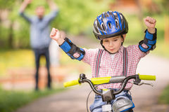 Father and son. Young father teaching son to ride bicycle in summer park Royalty Free Stock Image