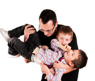 Father and sons. Father holding his two sons stock photo