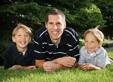 Father & Sons. Young caucasian father and two sons smiling and sitting on their elbows on the grass outdoors Royalty Free Stock Image