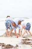 Father and sons on the beach playing in the sand Royalty Free Stock Image