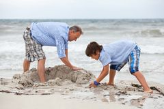 Father and sons on the beach playing in the sand Royalty Free Stock Photography