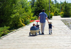 Father and Sons on the Boardwalk. Royalty Free Stock Image