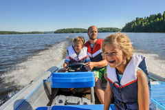Father and sons boating. Father and sons out boating together. The father lets one of the boys steer the boat. They're wearing life vests. In the background Royalty Free Stock Photos