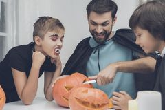 Father and sons carve pumpkins for a Halloween party royalty free stock photo