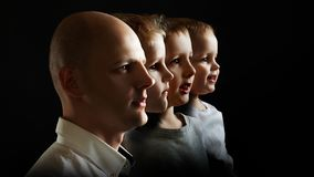 Father and sons, the concept of genetics and heredity. Young men and sons of different ages, portrait in profile on black background royalty free stock photography