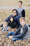 Father and Sons. Dad with his four sons sitting in the leaves at a park with a sidewalk in the background Stock Photography