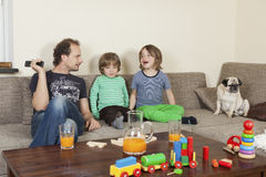 Father with sons and dog on sofa. In the foreground on a table toys and drinks Stock Photography
