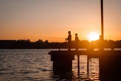 Father and sons fishing in the river at sunset, silhouette. Father and son fishing in the river at sunset Stock Image