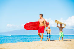 Father and Sons Going Surfing. Father and Two Young Sons Going Surfing at the Beach Royalty Free Stock Photo
