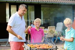 Father with sons grilling meat in the garden. A father with sons, two twin teenage boys cooking meat on barbecue for summer family dinner at the backyard of the Stock Image