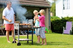 Father with sons grilling meat in the garden. A father with sons, two twin teenage boys cooking meat on barbecue for summer family dinner at the backyard of the Royalty Free Stock Photo