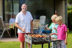 Father with sons grilling meat in the garden. A father with sons, two twin teenage boys cooking meat on barbecue for summer family dinner at the backyard of the Royalty Free Stock Photos
