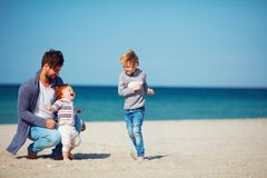 Father and sons having fun, running on the sandy beach royalty free stock image