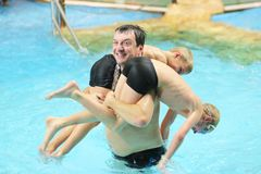 Father and sons having fun in swimming pool. Happy father with sons twin brothers having fun in the swimming pool Royalty Free Stock Photography