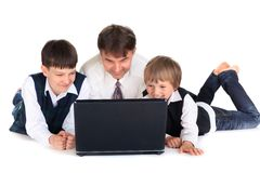 Father and sons with laptop. Father looking at laptop with two young sons, isolated on white background Royalty Free Stock Photos