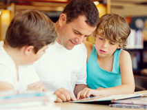 Father with sons in library Royalty Free Stock Photo