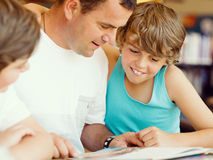 Father with sons in library Stock Images