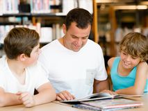 Father with sons in library Royalty Free Stock Images