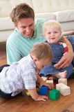 Father And Sons Playing With Coloured Blocks At Ho Royalty Free Stock Photos