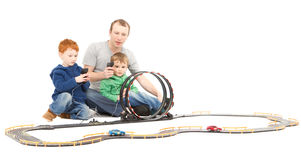 Father and sons playing kids racing toy car game. Father and children playing kids racing toy electric slot car game. On white Royalty Free Stock Image