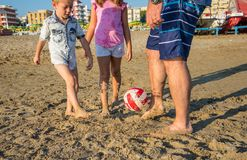Father and sons playing soccer on the beach royalty free stock photography