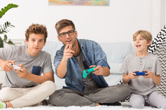 Father and sons playing together. Father and his sons holding controllers, playing video games together royalty free stock photos